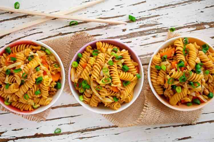 Top down view of 3 bowls of pasta stir fry.