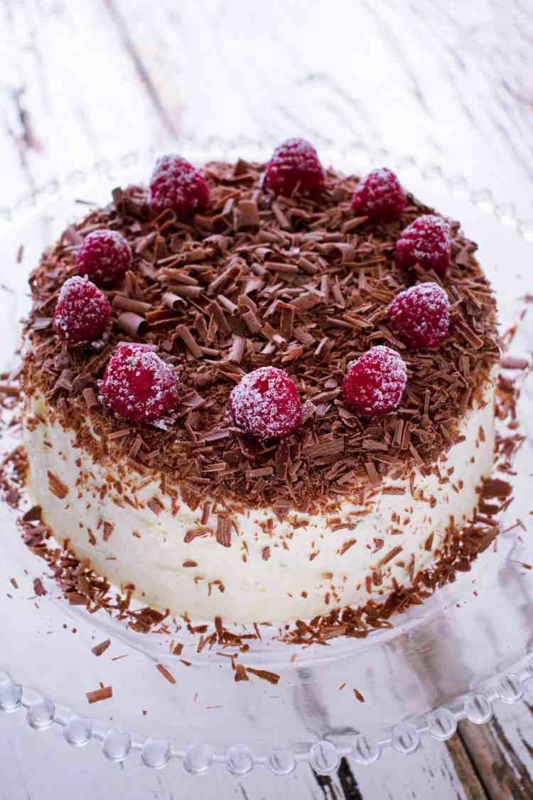 A 45 degree view of a chocolate ripple cake with chocolate shavings and fresh raspberries.
