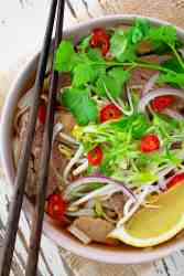 A bowl of beef pho, including rice noodles, beef, lemon wedge, beansprouts, chilli and fresh herbs.