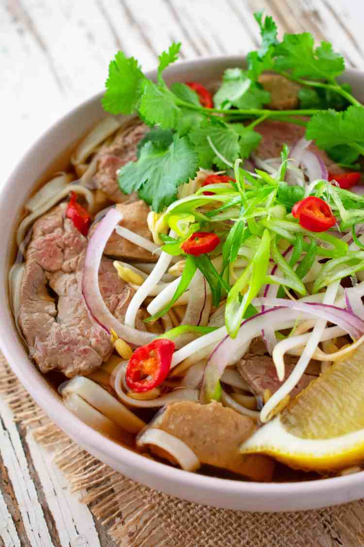 A bowl of quick beef pho, including rice noodles, beef, onions, beansprouts, lemon wedge and fresh herbs.