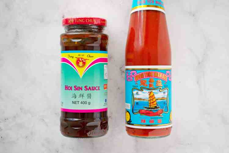 A picture of a bottle of hoi sin sauce and chill sauce.