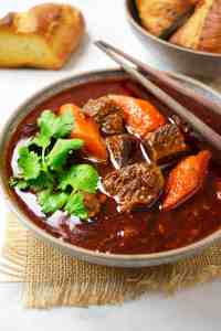 A bowl of bo kho garnished with fresh coriander, served with crusty bread.