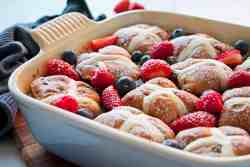 Hot cross bun pudding decorated with fresh berries