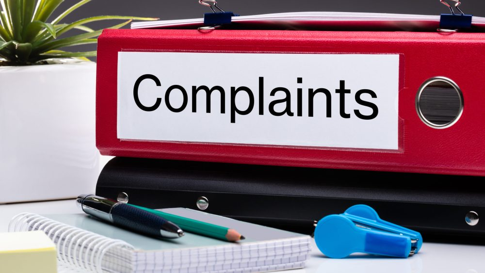 "office desk with binder labeled ""complaints"""