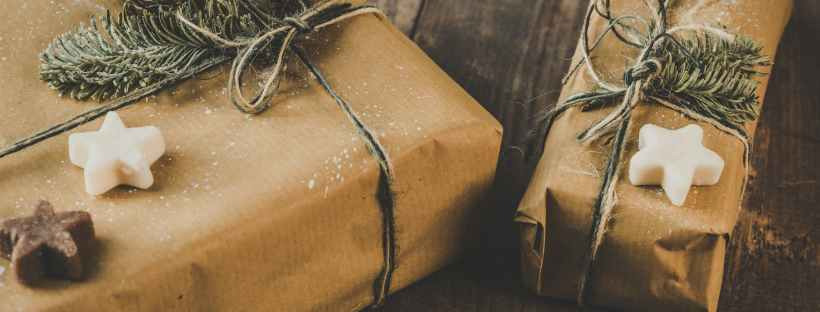 photo of two brown wrapped gifts on wooden table