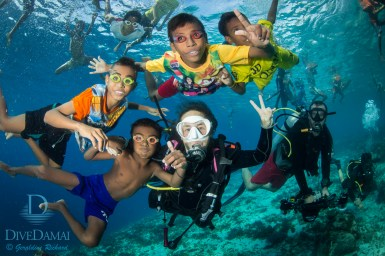 Kids love to ham for the camera with divers from the Damai II. Most of them are in homemade goggles, if any. (Geraldine Richard)