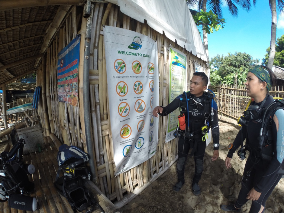 A divemaster conducts a briefing using the Green Fins poster before a dive in the Philippines. Courtesy of the Reef World Foundation