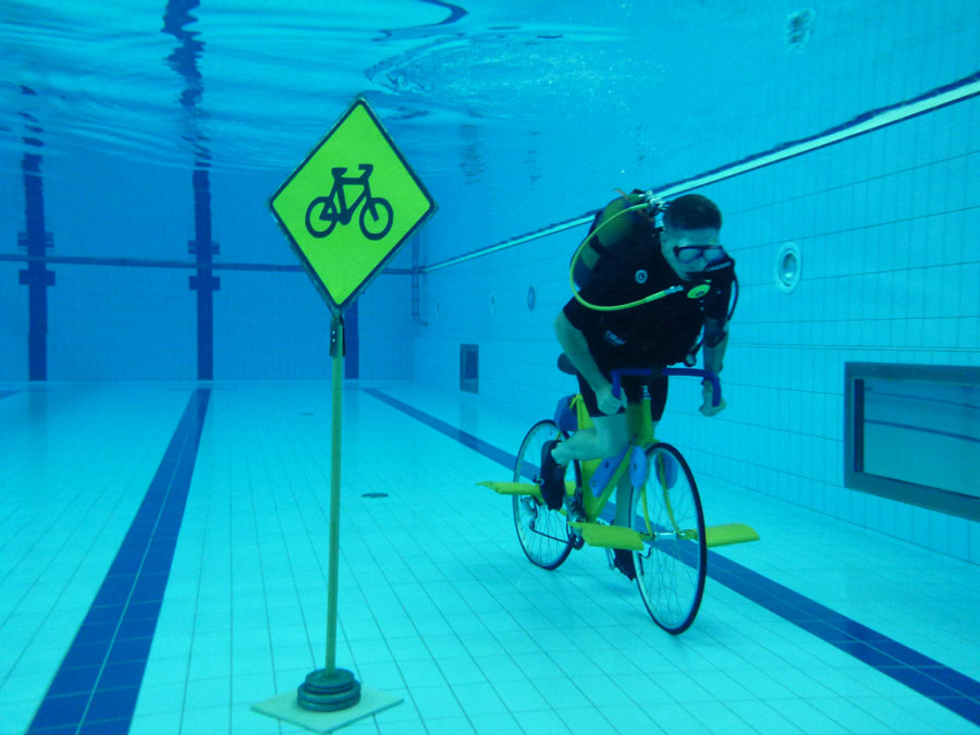 Ashrita Furman setting the record for longest distance to bicycle underwater (1.88 m/3.03 km) in September 2011. Photograph by Homagni Batista distributed under a CC BY-SA 3.0 license.