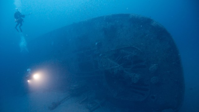 A NOAA diver on deck-level at E.M. Clark's stern showing exposed steering quadrant. Photo: Hoyt, NOAA
