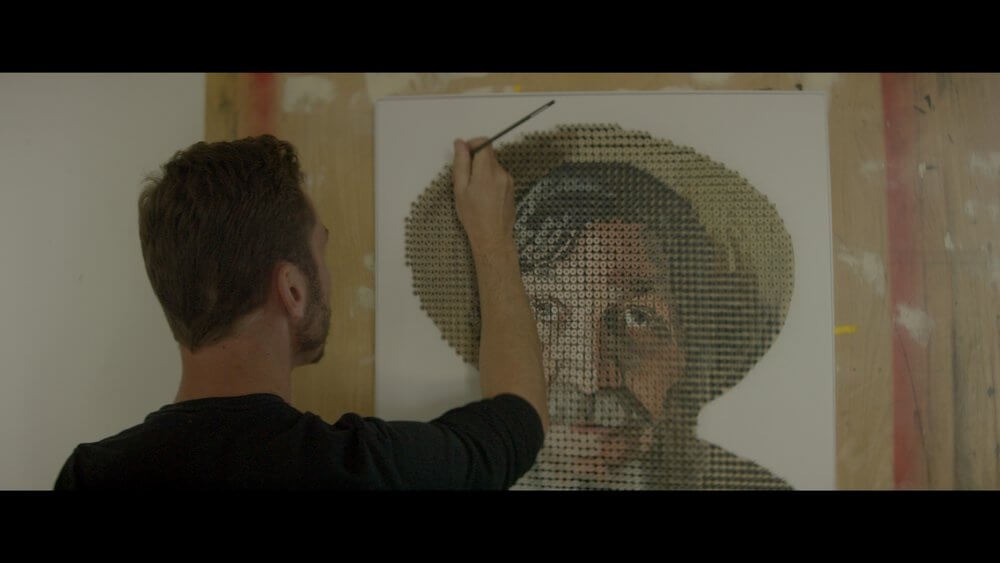 Andrew Myers painting screw heads on portrait of George Wurtzel