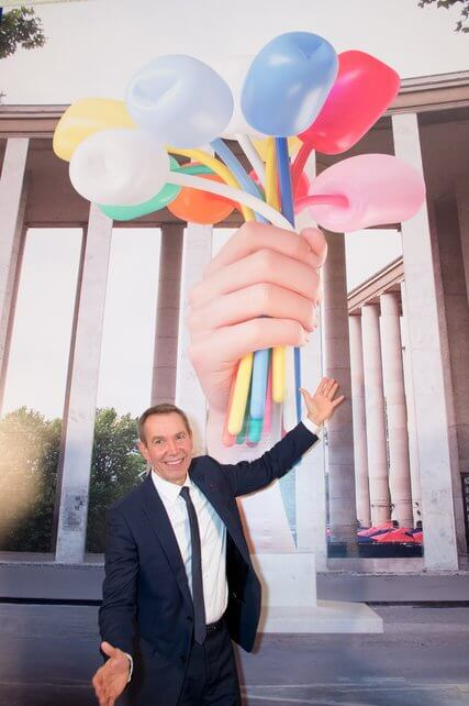 sculptor Jeff Koons in front of poster of his proposed piece Bouquet of Tulips