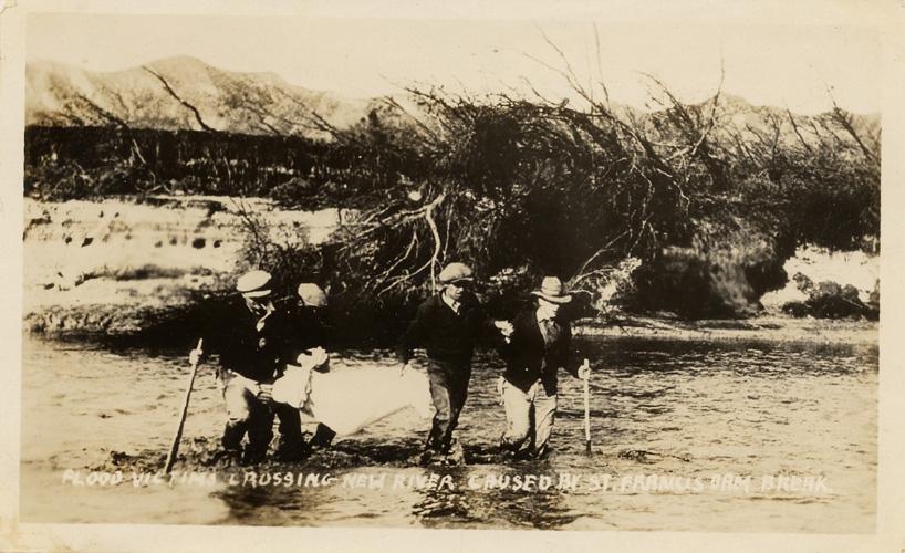 "Flood victims crossing river, March, 1928. Caption reads ""FLOOD VICTIMS CROSSING NEW RIVER CAUSED BY ST. FRANCIS DAM BREAK"""