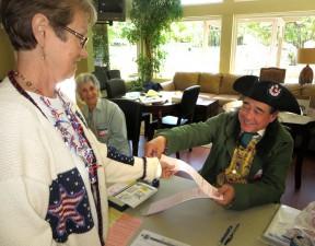 Poll worker Scott Ferguson hands a ballot to Sue Wameling as Joann Heller looks on at Scenic Hills.