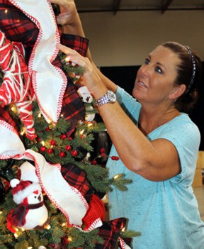 Ronda Chobanian, development director of the Boys & Girls Club of Santa Clarita Valley Foundation, decorates a Christmas tree for Festival of Trees. Photos: Michele E. Buttelman.