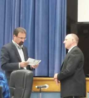 Acton-Agua Dulce's superintendent and a board member peruse the Beverly Hills Courier article on their attempt to charter a school in 90210 land.