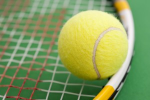 close up on a tennis ball resting on the strings of a tennis racket