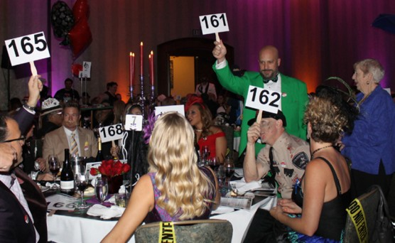 """Guests at the """"Clue"""" table raise their bidding paddles to support the """"Buy a Bus"""" campaign."""