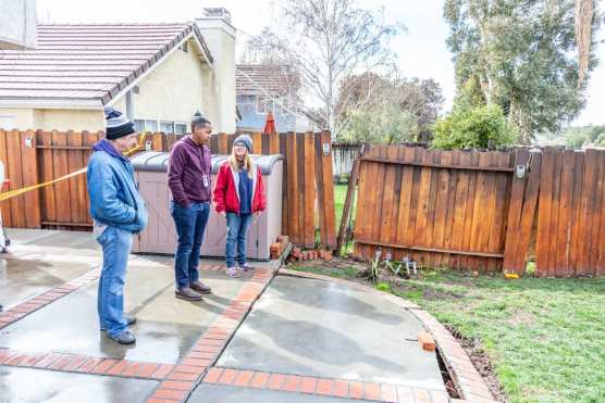 Homeowners stand with Signal reporter Austin Dave viewing the damage that is the result of a land slide that threatens multiple houses on Terri Drive as well as the Trestles housing development below in Canyon Country. | Photo: Cory Rubin/The Signal.
