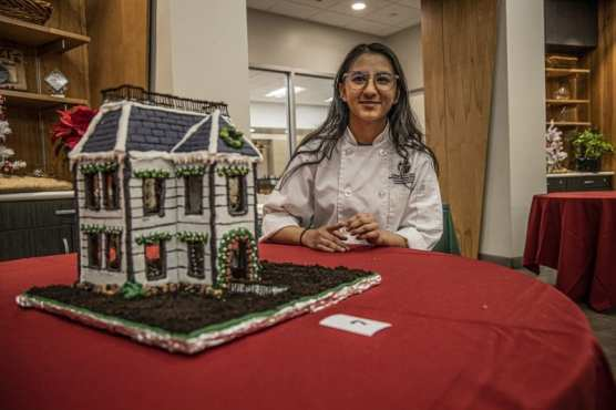 College of the Canyons Culinary Arts student Gina Rodriguez sits next to the elaborate Disney-inspired gingerbread house that she built for the school's second annual Gingerbread House Display and Competition Wednesday night, December 4, 2019. | Photo: Bobby Block / The Signal.