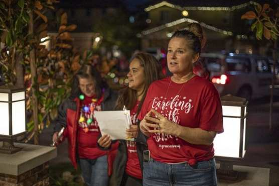 """Cindy Muehlberger, right, leads Lennette Moreno, middle, and a group of other carolers knocking on doors to collect non-perishable food as part the """"Caroling with Gracie"""" caroling for cans event set up in honor of Muehlberger's daughter Gracie, who was killed in the Saugus High School shooting last month. December 11, 2019. Bobby Block / The Signal."""
