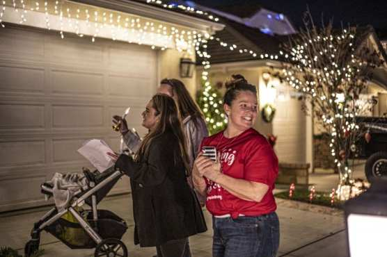 """Cindy Muehlberger, right, approaches a house with a group of fellow carolers Wednesday night as part of the """"Caroling with Gracie"""" event which aims to collect non-perishable foods for Hart District students in need while honoring the memory of Muehlberger's daughter Gracie, who was murdered in the Saugus High School shooting on November 14. 