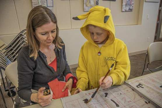 Diana Anderson sits with her son Tommy, age 7, as he participates in a crafts activity at the SCV Chinese School's Chinese New Year celebration at the Newhall Library on Saturday afternoon, January 18, 2020.   Photo: Bobby Block / The Signal.