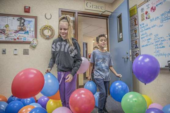 """Highlands Elementary School students Kyah Pollock and Martin Perez place balloons in principal Susan Bender's office as a reward for participating in the school's """"Great Kindness Challenge"""" on January 30, 2020. 