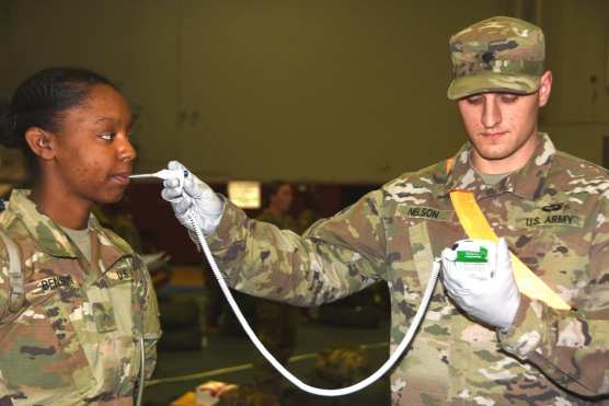 A recent graduate of the Army's basic combat training has her temperature taken upon arrival to Fort Lee, Va., March 31, 2020. | Photo: Army Master Sgt. Crista Mary Mack.