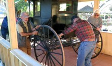 Volunteers roll the buggy into the carriage house.
