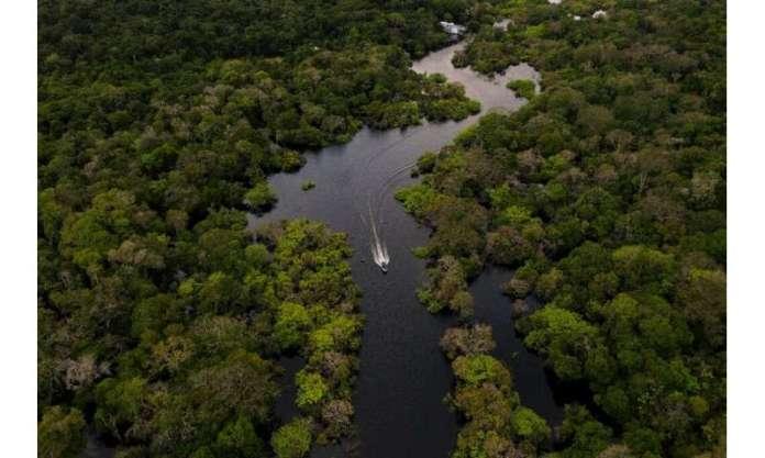 A boat accelerates the Jurura River in the Brazilian Amazon