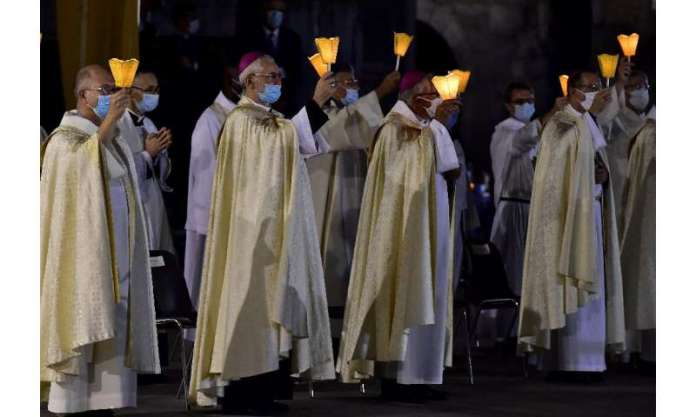 Prelates wearing face masks hold candles as they attend the 147th Assumption pilgrimage mass in France's Lourdes shrine on Augus