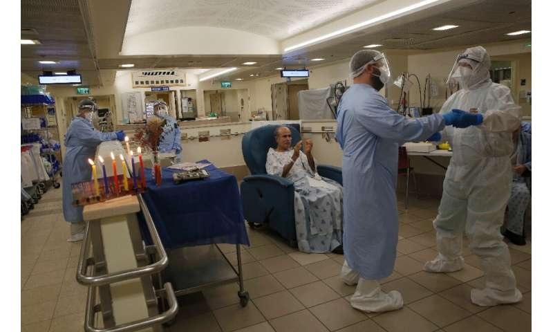Staff and patients celebrate after lighting Hanukkah candles at the COVID-19 isolation ward of Tel Aviv Sourasky Medical Center