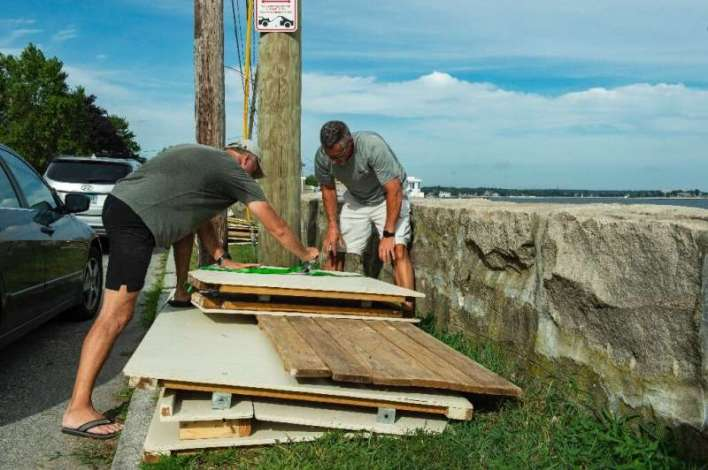 Members of a private beach association for Guthrie Beach tie down and disassemble beach huts prior to the arrival of Hurricane H