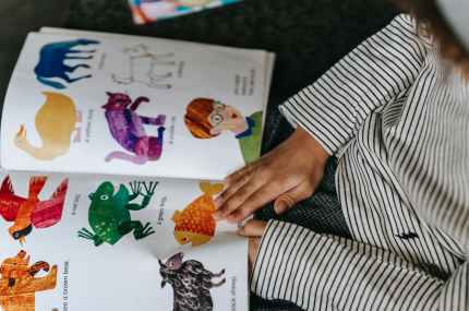 child watching bright pictures with animals in book