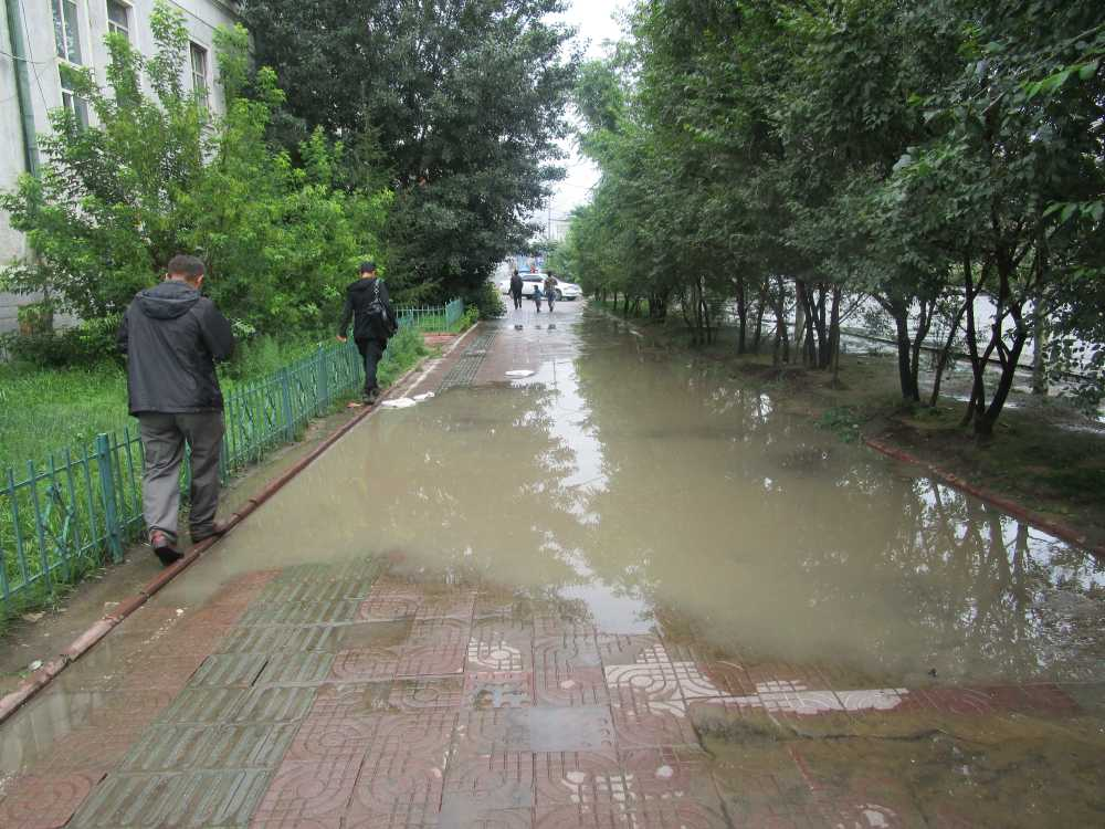 People avoiding water puddles after a downpour in Ulaanbataar.