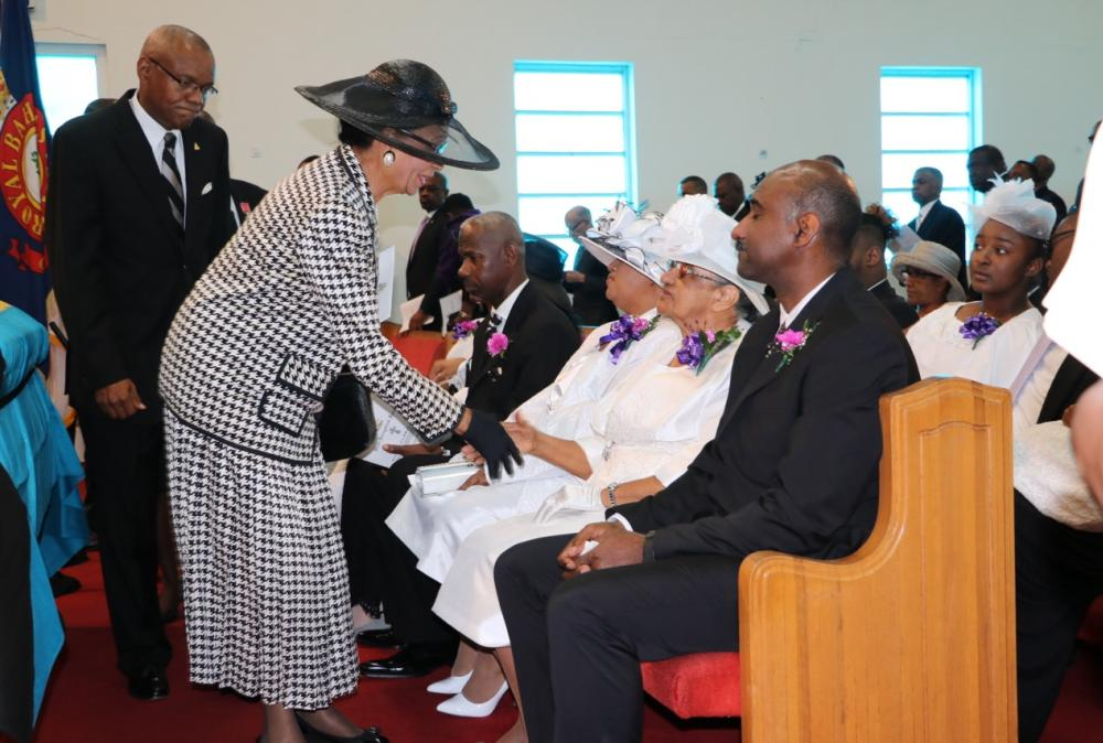 Governor General Marguerite Pindling greeting Ruth McKinney at the funeral while Atlantic Caribbean Union president Leonard Johnson follows behind.
