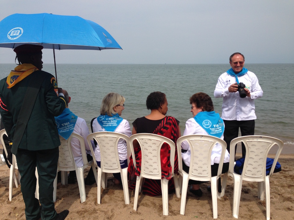 Duane McKey, standing right, taking photos of a mass baptismal ceremony at Rwanda's Lake Kivu in May 2016. (Andrew McChesney/Adventist Mission)