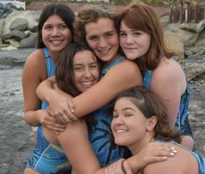 Girls smile and hug on the beac