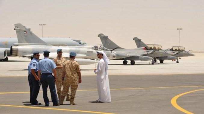 أفراد عسكريون إماراتيون يقفون بالقرب من مقاتلتين فرنسيتين من طراز رافال ومقاتلة ميراج 2000-9 إماراتية في قاعدة عسكرية بالقرب من أبو ظبي في 25 أيار /مايو 2009 (AFP)