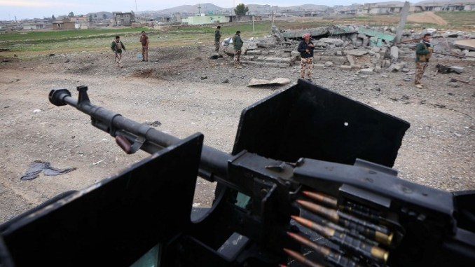 مقاتلو البشمركة يتجمّعون في موقع عملية انتحارية نفذها تنظيم الدولة الإسلامية في قرية كساريج جنوب مدينة زمار في محافظة نينوى شمال العراق بالقرب من الحدود مع سوريا في 18 كانون الأول/ديسمبر 2014 (AFP)