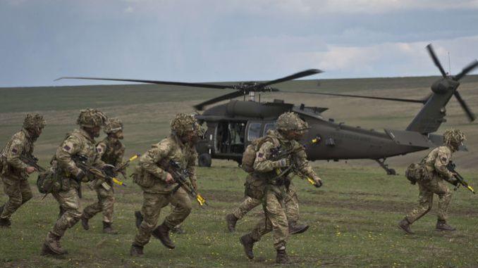 """جنود بريطانيون يتّخذون مناصبهم بعد نزولهم من مروحيات تابعة للجيش الأميركي خلال المناورات العسكرية لحلف شمال الأطلسي """"Wind Spring 15"""" في مجموعة سماردان العسكرية في 21 نيسان/أبريل 2015 (AFP)"""