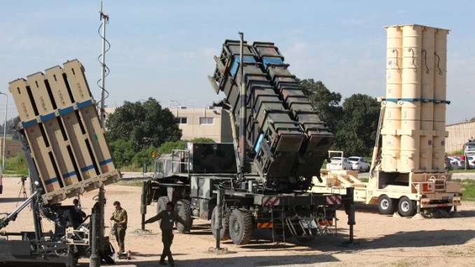 """جنود إسرائيليون يسيرون بالقرب من نظام """"القبة الحديدية"""" (إلى اليسار) ونظام الصواريخ أرض-جو MIM-104 Patriot (في الوسط) والصاروخ المضاد للصواريخ البالستية """"أرو-3"""" خلال التدريب العسكري Juniter Cobra في 25 شباط/فبراير 2016 (AFP)"""