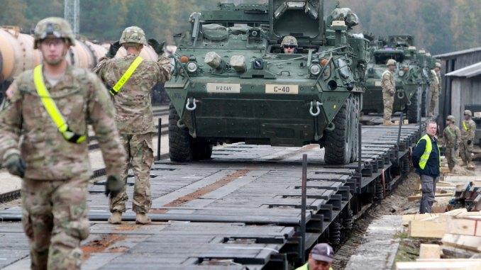 أفراد من اللواء الأول بالجيش الأميركي، فرقة الفرسان الأولى، يفرغون مركبات سترايكر المدرعة في محطة السكك الحديدية بالقرب من قاعدة روكلا العسكرية في ليتوانيا في 4 تشرين الأول/أكتوبر 2014 (AFP)