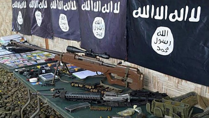 صورة تم التقاطها في 26 تشرين الثاني/نوفمبر 2015، تظهر فيها أسلحة وأعلام تنظيم داعش المستردة من أعضاء عصابة إجرامية تعهدت بالولاء لداعش في بلدة باليمبانج، إقليم سلطان كودارات، في جزيرة مينداناو الجنوبية (AFP)