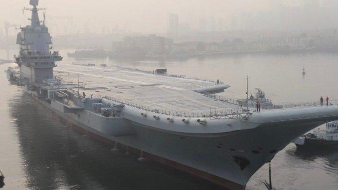 أول حاملة طائرات مصنعة محليا لدى مغادرتها ميناء داليان في 13 أيار/ مايو (رويترز).
