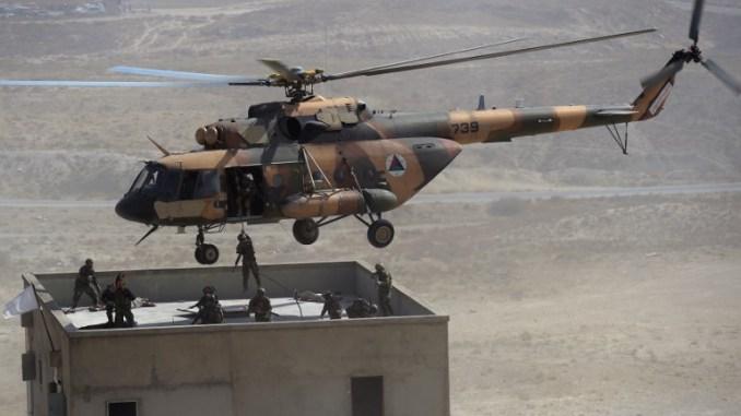 """قوات الجيش الوطني الأفغاني تتخذ مواقعها بعد النزول من مروحية """"مي-17"""" روسية خلال مناورة عسكرية في مركز التدريب العسكري (KMTC) في ضواحي كابول يوم 17 تشرين/الأول أكتوبر 2017 (AFP)"""