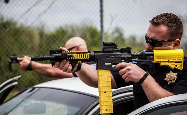 صورة غير مؤرخة من شركة PepperBall Technologies تُظهر ضابط شرطة يستخدم النظام الحركي المتغير، الذي يطلق النار على أو مقذوف على شكل مملوء بمسحوق الفلفل الذي ينفجر ويخلق سحابة من البودرة عند الاصطدام. (شركة PEPPERBALL)