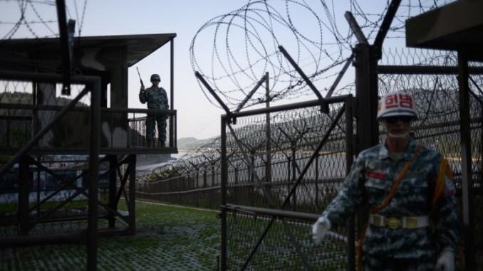 مجسمات عن جنود كوريين جنوبيين أمام مركز حراسة مفتوح للزوار، بجانب السياج الشائك في المنطقة المنزوعة السلاح (DMZ) بين كوريا الشمالية والجنوبية في جزيرة كانغهوا في 24 أيار/مايو 2018 (AFP)