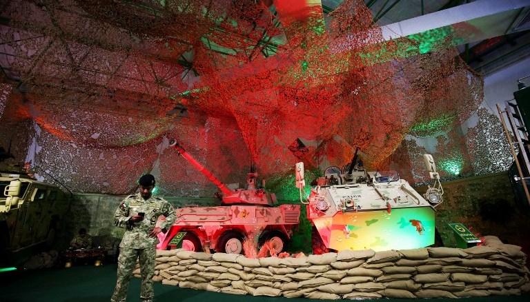 صورة تم التقاطها في 12 كانون الأول/ديسمبر 2017 تُظهر جنديًا كويتيًا يقف أمام العربات المدرعة وقطع المدفعية المتنقلة التي عرضتها القوات المسلحة الكويتية في معرض الخليج للدفاع والفضاء الجوي الذي أقيم في أرض المعارض الدولية في مدينة الكويت (AFP)