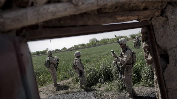 عناصر من الكتيبة الثالثة تابعين للبحرية الأميركية تتحقق من موقعها على جهاز GPS في حين تتحرك إلى الأمام في مزرعة خلال دورية راجلة في مارجا، إقليم هلمند، في 3 نيسان/أبريل 2010 (AFP)